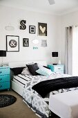 Double bed with black and white bed linen, turquoise blue bedside tables and various wall decorations in the bedroom