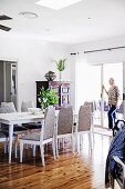 Dining area with upholstered chairs on shiny wooden floor, woman in front of sliding patio door