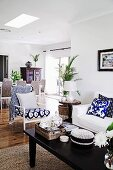 Open living area with dark-colored coffee table and blue and white patterned armchair