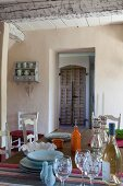 Glasses and crockery on table in front of open door with view of cupboard with rustic, slatted wooden door
