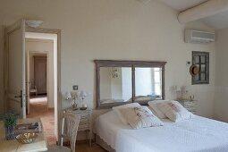 Double bed below framed mirror in rustic bedroom