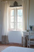 Floor-length curtains on open lattice window and vintage desk and chair in bedroom