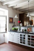 Kitchen counter with white, country-house-style base units and raised bar below pendant lamps