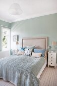 Double bed with upholstered headboard against pastel-green wall in bedroom