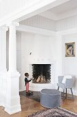 Grey pouffe and armchair in seating area next to fireplace next to white, antique-style column