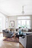 Grey armchairs around black coffee table in rustic, elegant living room