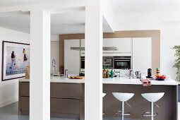Island counter, white worksurface on brown base unit and bar stools in open-plan kitchen in loft-style apartment