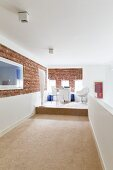 And open-plan workspace on platform on gallery with strip of exposed brick wall