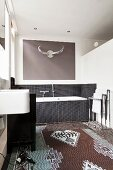 Patterned rug, bathtub with black-tiled surround and stylised hunting trophy in modern bathroom