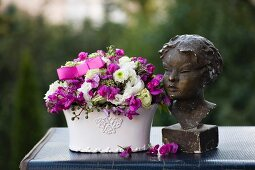 Romantic flower arrangements and bust of woman on top of vintage suitcase outdoors