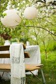 Garden bench below lanterns hanging in blossoming fruit tree