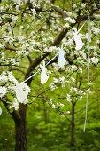 Garland of bunnies between blossoming fruit trees