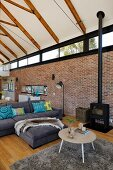 Coffee table, flokati rug and grey sofa in lounge area of open-plan interior with exposed roof structure and brick wall