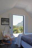 Rocking chair and standard lamp next to open balcony door in bedroom