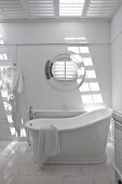 White bathroom with porthole window and vintage-style free-standing bathtub