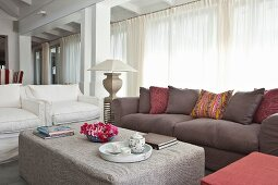 Comfortable elegant living area with upholstered seating, ottoman and white curtains on glass wall