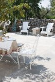 White metal chairs and breakfast table on sunny terrace with outdoor armchairs against stone wall