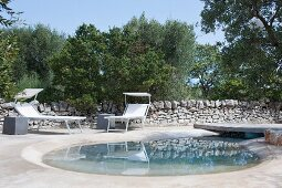 Sun loungers on concrete terrace with teardrop-shaped plunge pool