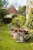 Potted plants on rim of old well in garden with historical manor house in background