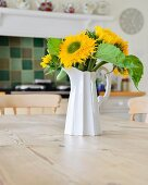 White jug of sunflowers on wooden table in country-house kitchen