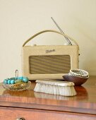 Jewellery in dish and clothes brush in front of retro portable radio