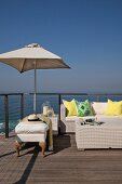Comfortable outdoor lounge furniture on sun deck with sea view under blue sky