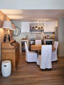 Comfortable country-house kitchen with white loose-covered chairs and plain wooden furniture