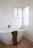 Dark brown towel draped over white free-standing designer bathtub on oak parquet floor below corner windows with shutters