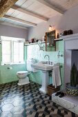 Pastel green wall tiles, pedestal sink and 3D-patterned floor tiles in vintage bathroom