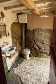 Partially rendered rock walls in Mediterranean bathroom