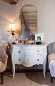 Table lamp and mirror on antique white chest of drawers