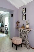 Antique stool with striped upholstery next to console table with ornamental base against lilac wall