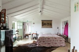 Patterned bedspread on double bed below white wooden ceiling in converted attic