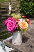 Roses and carnations in vintage jug on rustic garden table