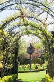 Climber-covered trellis arches framing dovecot in spring garden