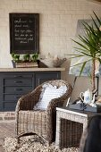 Wicker armchair and side table in front of white brick wall