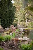 Sculpture in garden pond next to yew tree