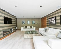 White leather sofa, stripes wallpaper and gas fireplace in luxurious interior