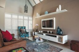 Brown sofa, patterned armchair, curved glass table, sideboard and flatscreen TV on pale brown wall
