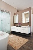 Spacious bathroom with walls painted pale brown, rug in front of washstand and glazed shower area