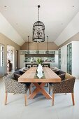 Leopard-print armchairs at long wooden table below pendant lamp with bird-cage lampshade in open-plan interior