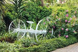 Old agricultural vehicle painted white in flowering garden