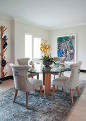 Chairs with pale upholstery at round glass table on rug in dining room with minimalist ambiance