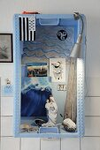Arrangement of beach finds and souvenirs in old herring crate on wall