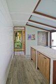 Custom sideboards with wooden doors in open-plan hallway leading to open door with view of artwork