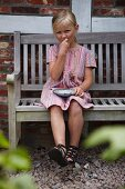 Blonde girl wearing pin summer dress sitting on rustic wooden bench