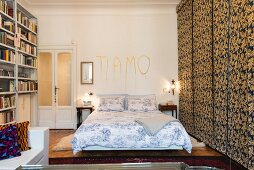 Double bed below lovers' message on wall and next to fabric sliding elements in bedroom