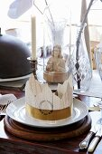 Place setting with party hat on white plate in front of Jesus figurine under glass cover
