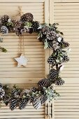 Festive wreath of pine cones with star pendant hung in vintage louvre door