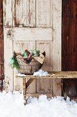 Metal basket of pine cones and Christmas-tree baubles in front of old door